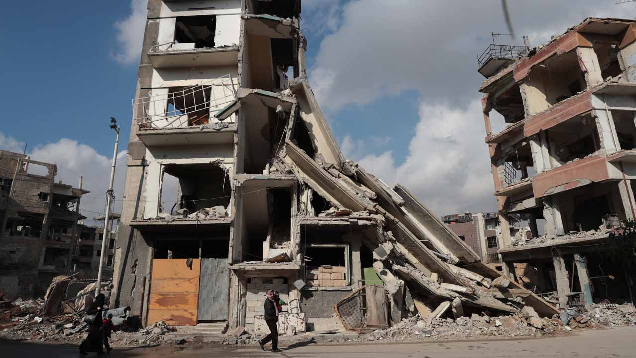Syrians walk past a destroyed building in the rebel-held town of Douma, on the eastern outskirts of Damascus, on December 30, 2016, on the first day of a nationwide truce. Clashes erupted between Syrian government forces and opposition fighters in an area outside Damascus, despite a nationwide truce that began at midnight, a monitor said. Abd Doumany / AFP