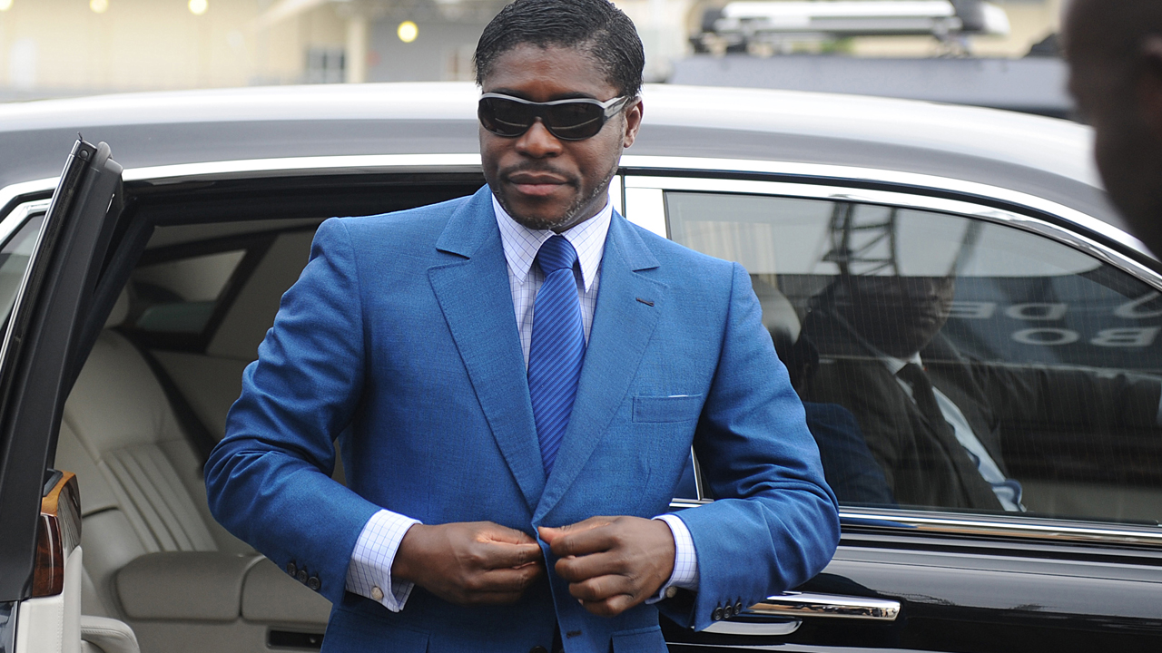 """(FILES) This file photo taken on June 24, 2013 shows Teodoro (aka Teodorin) Nguema Obiang Mongue, the son of Equatorial Guinea's president, arriving at Malabo stadium for ceremonies to celebrate his 41st birthday. Obiang will go on trial in a Paris court on January 2, 2017 in a case of """"ill-gotten gains"""". / AFP PHOTO / JEROME LEROY"""