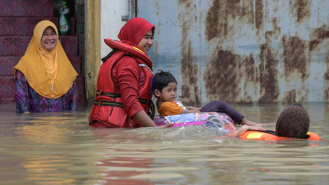 A family swims in floodwaters in Bendang Pak Yong, Malaysia's northeastern town of Tumpat, which borders with Thailand, on January 6, 2017. Serious flooding in Malaysia's northeast states for almost a week is showing some respite but has damaged homes, caused loss of income and disrupted schooling, victims said on January 6. Mohd RASFAN / AFP
