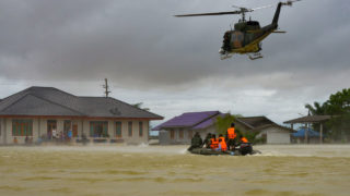 This photo, taken on January 7, 2017 shows a rescue boat and a helicopter moving towards a group of stranded people in the Srinakarin district of the southern Thai province of Phattalung. / AFP PHOTO / DAILYNEWS / Thailand OUT /
