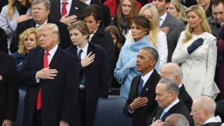 US President Donald Trump (L) and former US President Barack Obama cross their hearts during the National Anthem sung at Trump's swearing-in ceremony on January 20, 2017 at the US Capitol in Washington, DC.  Mark RALSTON / AFP