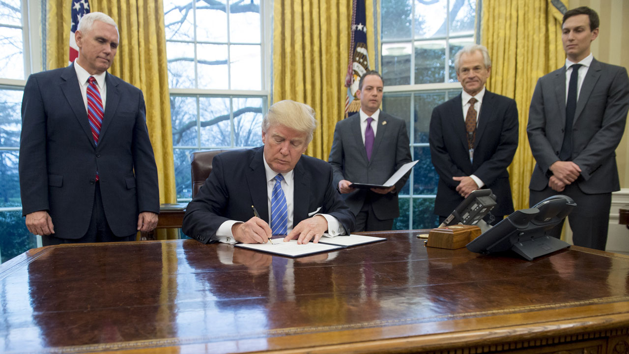 US President Donald Trump signs an executive order for a federal hiring freeze alongside White House Chief of Staff Reince Priebus (C), US Vice President Mike Pence (L) and Senior Advisor Jared Kushner(R) in the Oval Office of the White House in Washington, DC, January 23, 2017. Trump signed the decree Monday, effectively ending US participation in a sweeping trans-Pacific free trade agreement negotiated under former president Barack Obama. SAUL LOEB / AFP