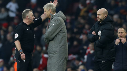 Arsenal's French manager Arsene Wenger (2nd L) is sent to the stands by English referee Jonathan Moss (L) as fourth official Anthony Taylor (R) looks on during the English Premier League football match between Arsenal and Burnley at the Emirates Stadium in London on January 22, 2017.  Arsenal won the game 2-1. / AFP PHOTO / Ian KINGTON /
