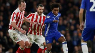 Chelsea's Brazilian midfielder Willian vies with Stoke City's Scottish midfielder Charlie Adam (L) and Stoke City's Dutch defender Erik Pieters (2nd L) during the English Premier League football match between Chelsea and Stoke City at Stamford Bridge in London on December 31, 2016. Chelsea won the game 4-2. Adrian DENNIS / AFP