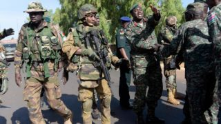 Soldiers from The Gambia shake hands, as to show respect to ECOWAS (Economic Community of West African States) soldiers, in front of the Second Infantry Battalion Camp in Farafegny on January 22, 2017. Gambian leader Yahya Jammeh flew out January 21 from the country he ruled for 22 years to cede power to President Adama Barrow and end a political crisis. Jammeh refused to step down after a December 1 election in which Barrow was declared the winner, triggering weeks of uncertainty that almost ended in a military intervention involving five other west African nations. SEYLLOU / AFP