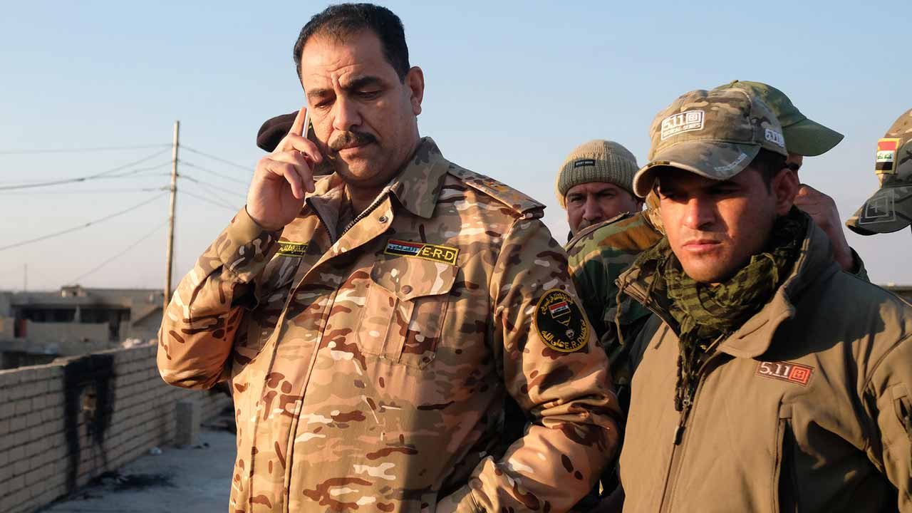 Iraqi Major General Thamer Mohammed Ismail (L), Commander of the Rapid Response Division, talks on the phone at a position in southern Mosul, on January 4, 2017. Iraqi forces have retaken more than 60 percent of eastern Mosul from the Islamic State group since the battle for the city began in mid-October, a top commander saidon January 1. Ahmad MOUSA / AFP