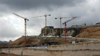 (FILES) This file photo taken on January 27, 2016 shows cranes at a construction site in the Israeli settlement of Ramot built in a suburb of mostly Arab east Jerusalem. Israeli authorities on January 22, 2017, approved building permits for 566 settler homes in annexed east Jerusalem, plans that had been postponed until US President Donald Trump took office, the city's deputy mayor Meir Turjeman said.  The new permits are for homes in the settlement neighbourhoods of Pisgat Zeev, Ramot and Ramat Shlomo, according to Turjeman, who also heads the planning committee that approved them.  AHMAD GHARABLI / AFP