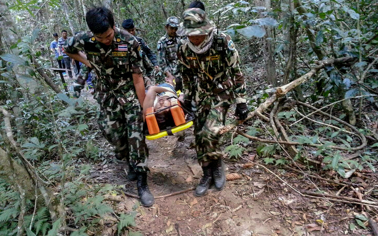 In this hand out photo by Thai authorities of the Khao Yai National Park of January 1, 2017, French national Muriel Benetulier is transported on a stretcher by Thai Park Rangers after she was bitten by after she was bitten by a crocodile. Benetulier was bitten by a crocodile inside the Thai national park as she tried to get close to the fearsome animal to take a selfie, an official said. / AFP PHOTO / HO /