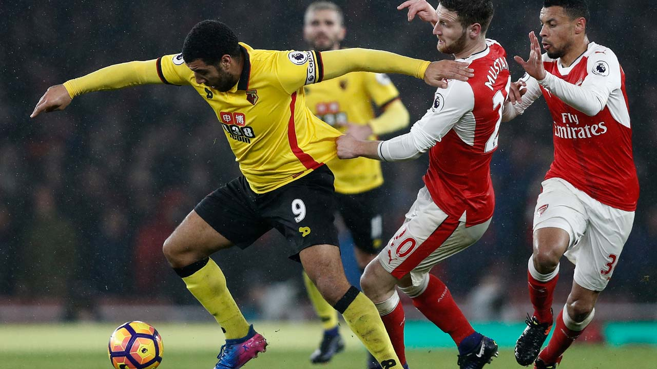 Watford's English striker Troy Deeney (L) vies with Arsenal's German defender Shkodran Mustafi (C) and Arsenal's French midfielder Francis Coquelin during the English Premier League football match between Arsenal and Watford at the Emirates Stadium in London on January 31, 2017. Watford won the match 2-1. PHOTO: Adrian DENNIS / AFP